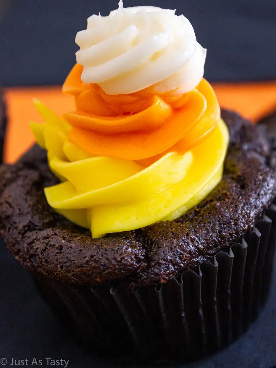 Close-up of a chocolate Halloween cupcake topped with yellow, orange, and white swirl buttercream.