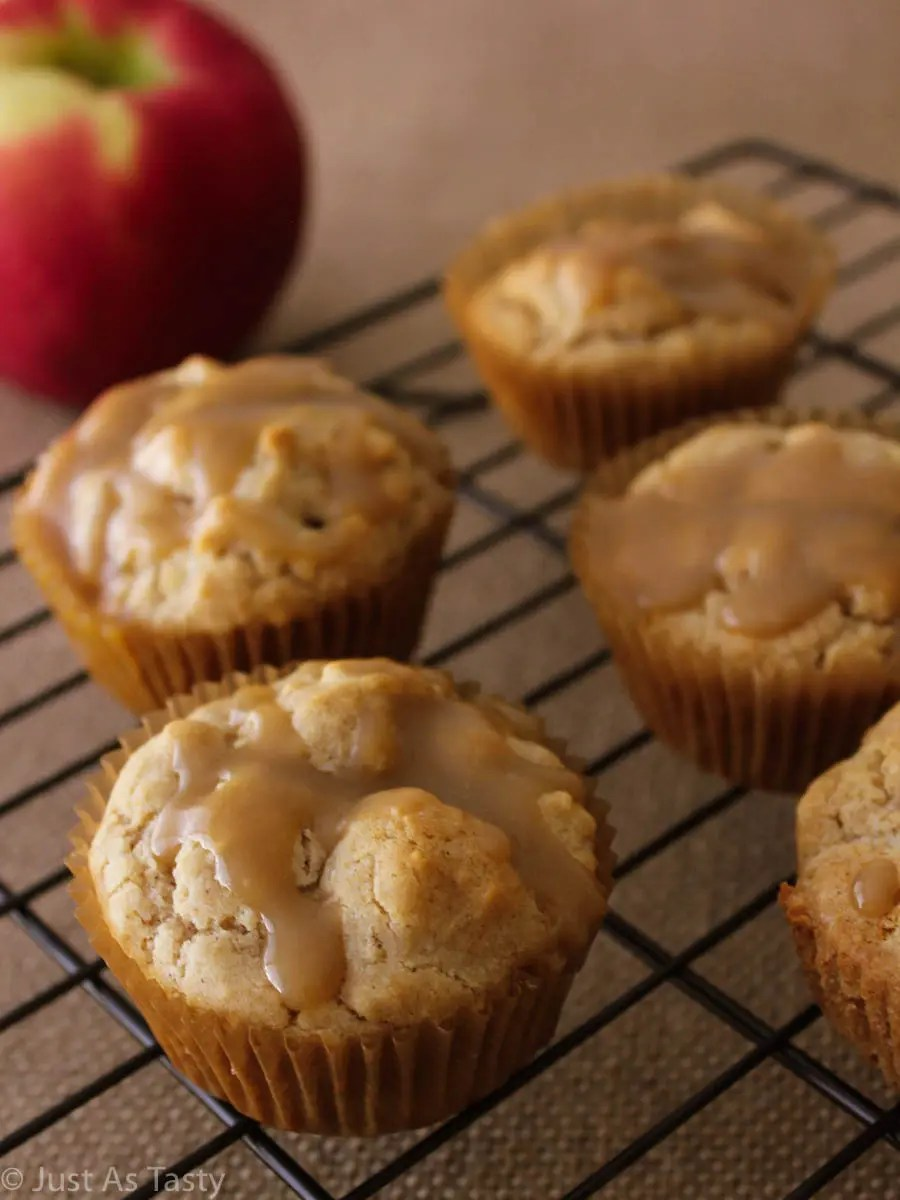 Easy apple muffins topped with caramel sauce on a black wire cooling rack.