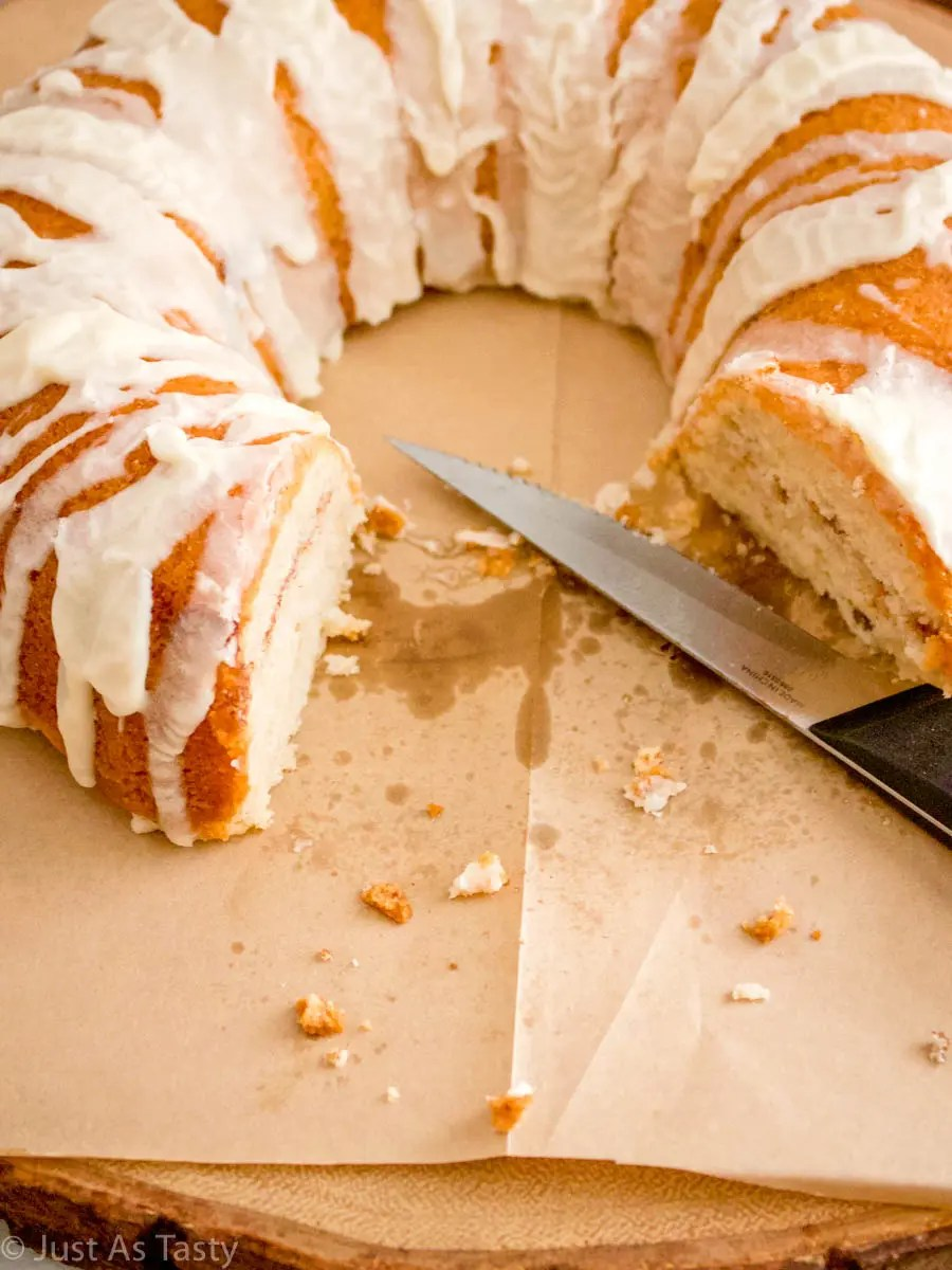 Gluten free cinnamon roll cake with a piece missing.