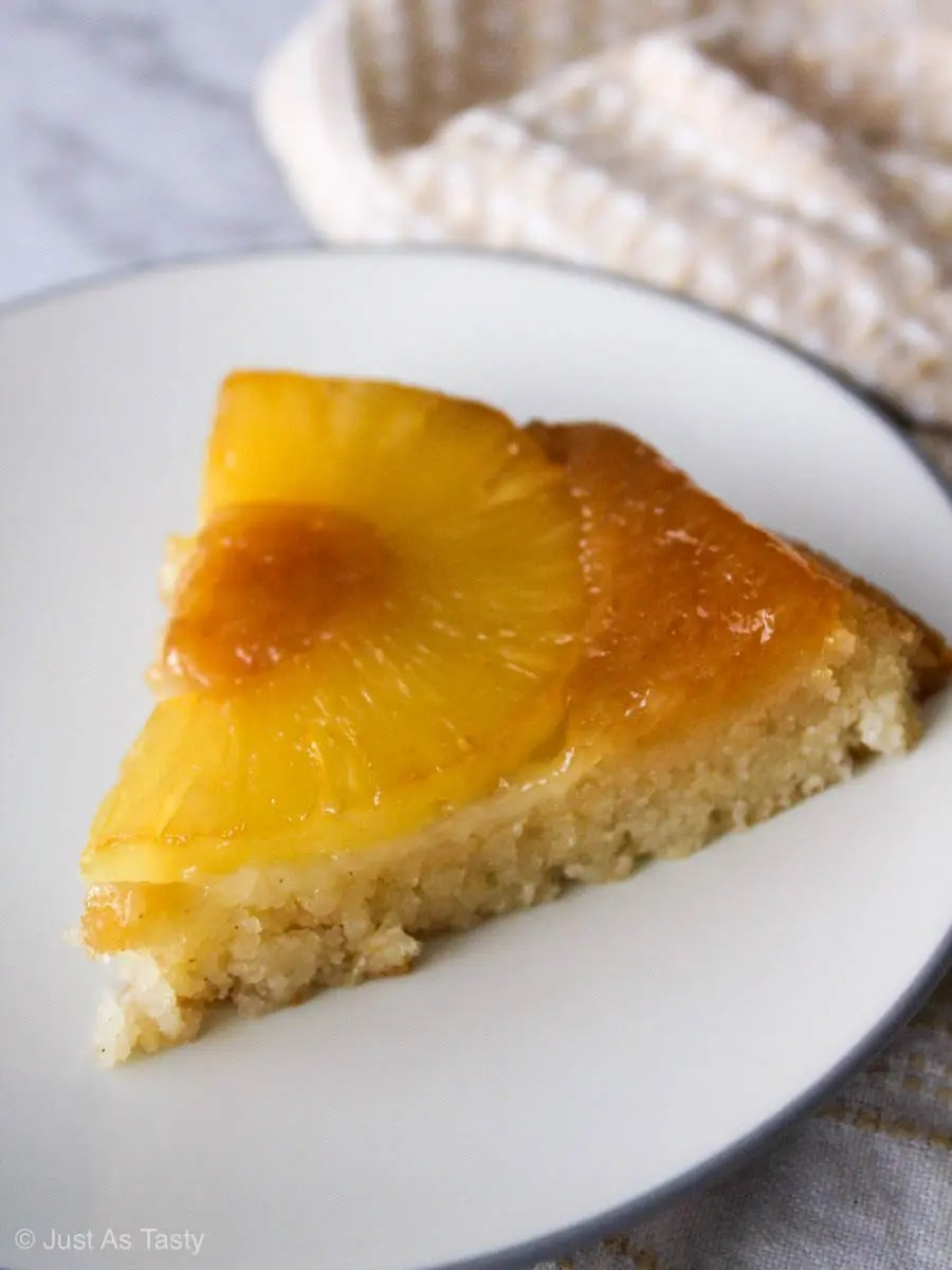 Slice of pineapple upside down cake on white plate.