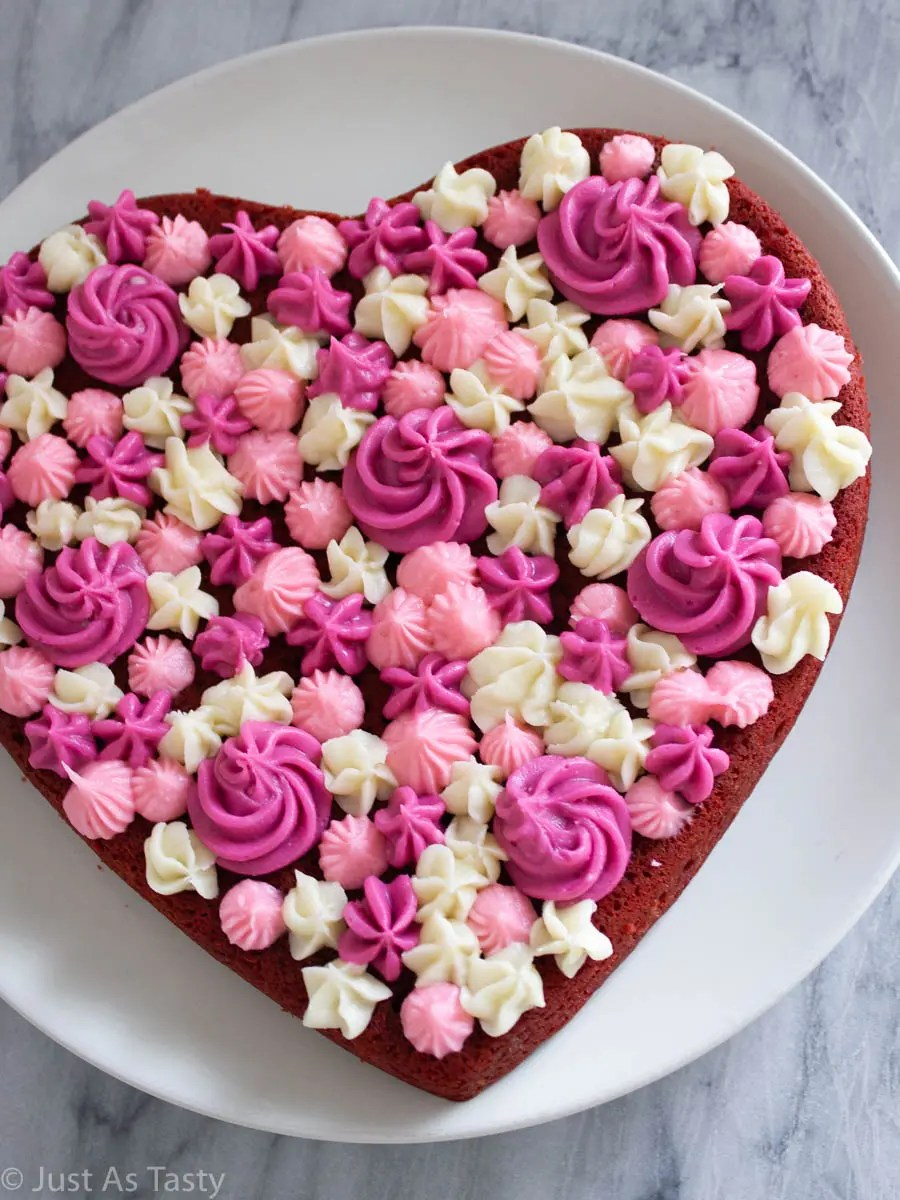 Heart shaped gluten free red velvet cake with pink and white piped frosting on top.