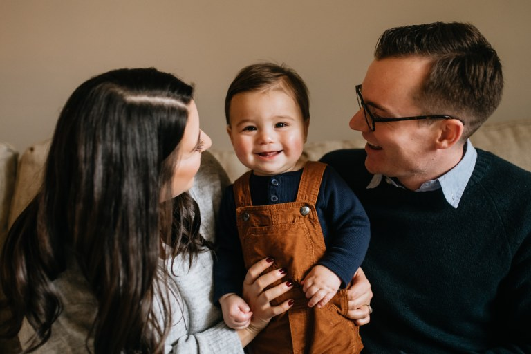 Baby smiling with parents looking at him