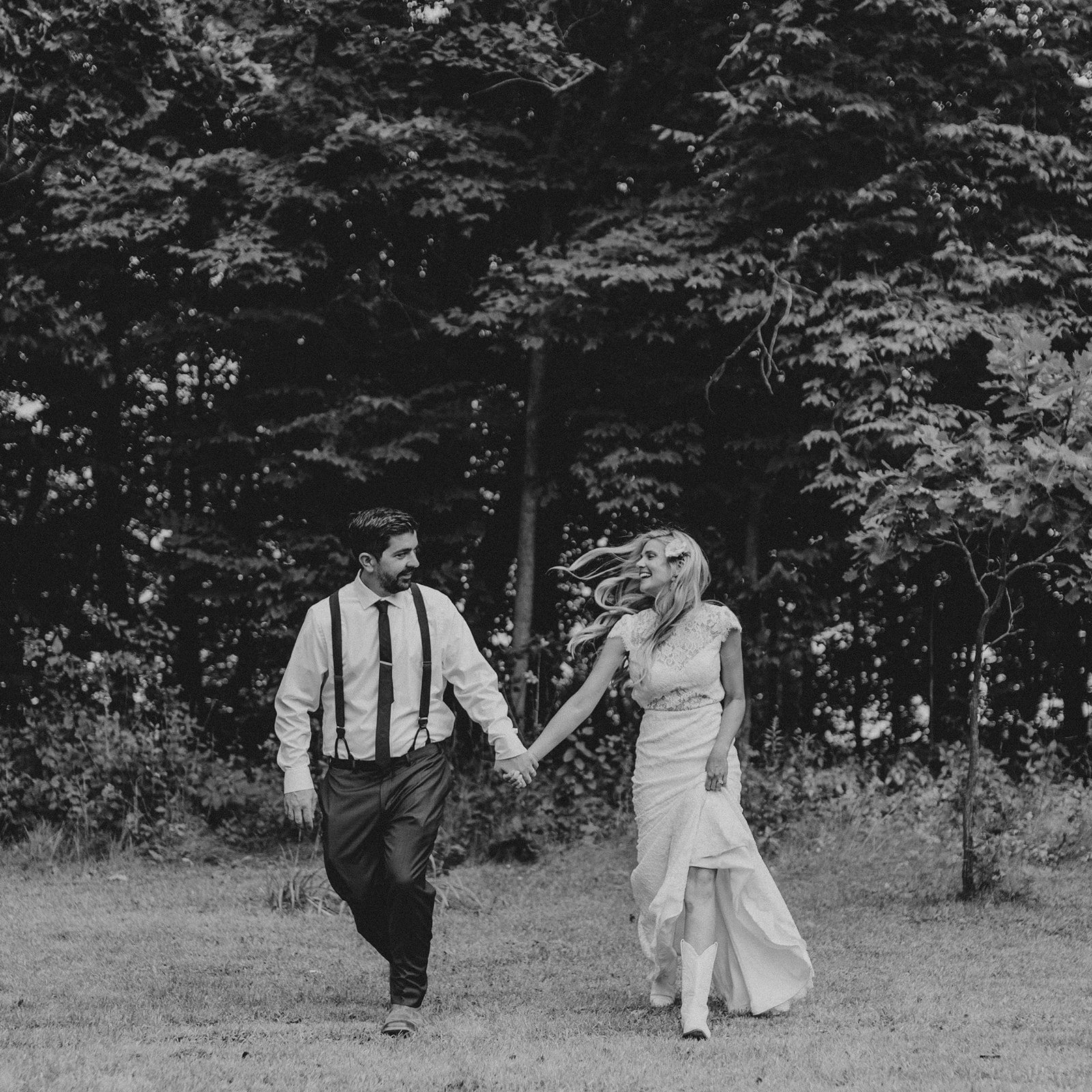 bride and groom run while holding hands