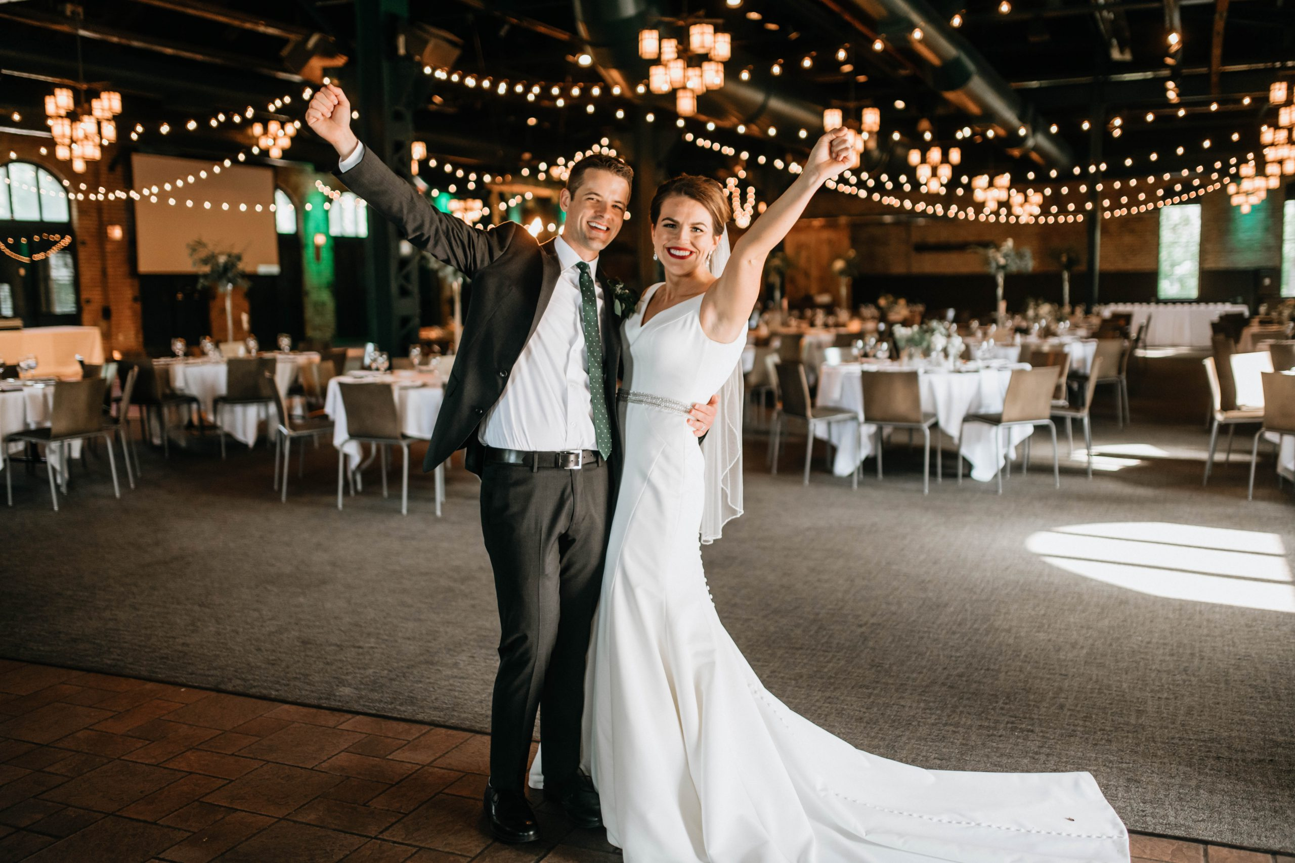 bride and groom throw their arms up at their reception