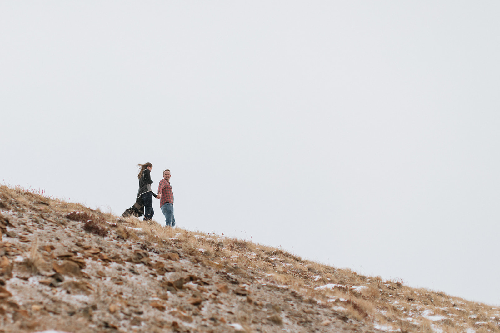 couples walks down hillside in the mountains of colorado