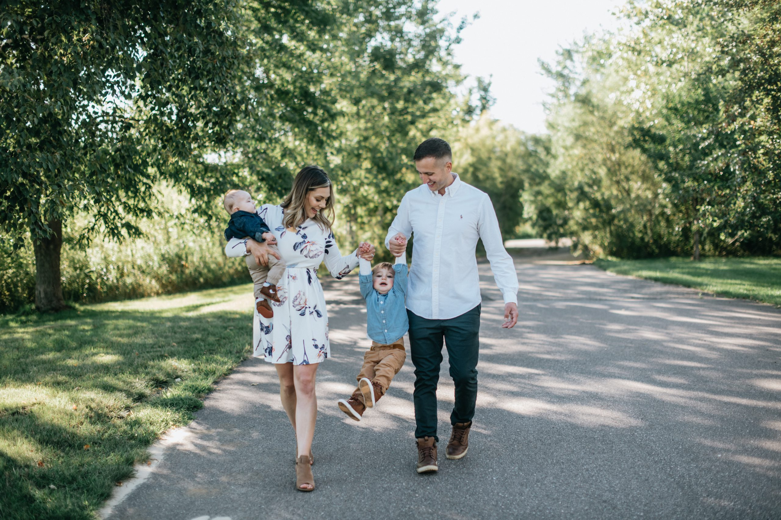 family walking and swinging their toddler by his hands.