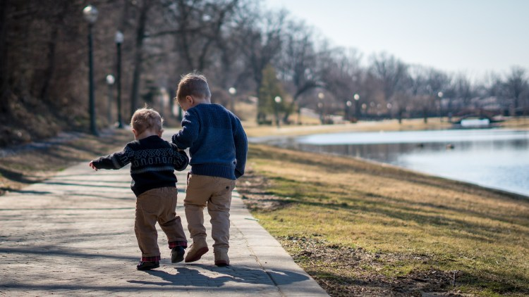 two preschool boys holding hands and walking down a path