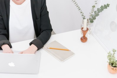 a woman working at a white desk
