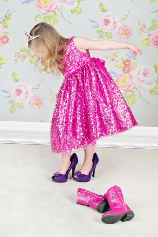 little girl in pink dress trying on mother's high heels