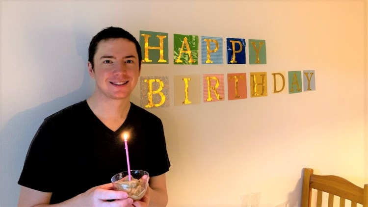 Benjamin standing in front of a wall with birthday decorations