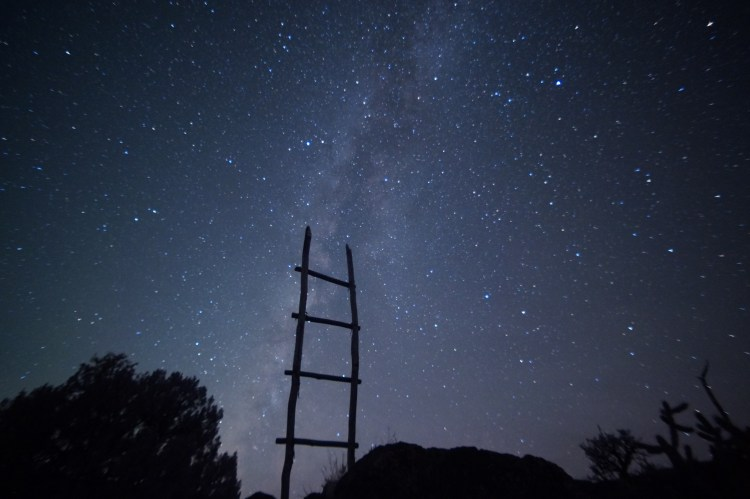 a starry sky with a ladder standing up against a wall towards heaven