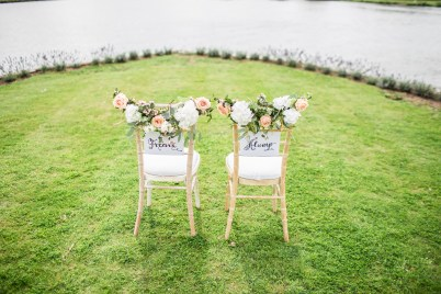 two wedding chairs sitting on a lawn