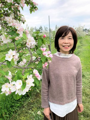 Mum standing by an apple tree with blossoms