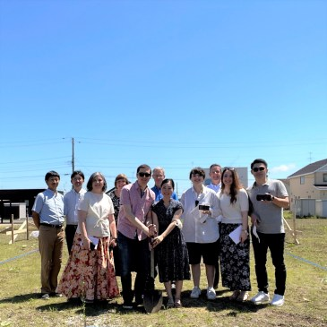 group photo of groundbreaking attendees under a blue sky