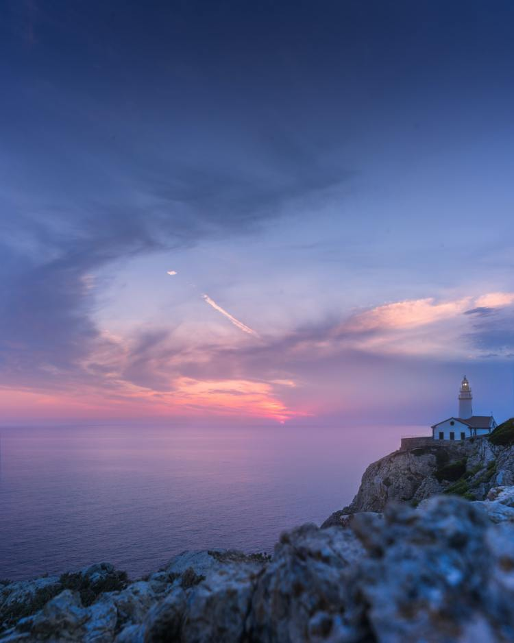daybreak over an ocean with a lighthouse on the cliff