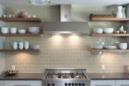 open shelving on glass tile kitchen wall