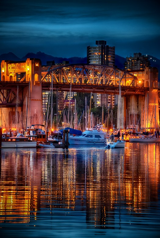 This is Burrard Bridge as viewed from the Granville harbor in Vancouver. I took this one summer evening while exploring the shops and sights of Granville market which is a must see when you go to Vancouver. In some ways this shot is a summary of the city, in the forefront are the boats, followed by the bridge, then behind that buildings of the city and finally all the way back are the mountains surrounding Vancouver. Of course there is a lot more to the city but this was my perspective at that moment. In any case, when exploring this part of the city the only danger you might run into is running out of time as quite often happens to me when I have my camera. But, I suppose that's a good thing.