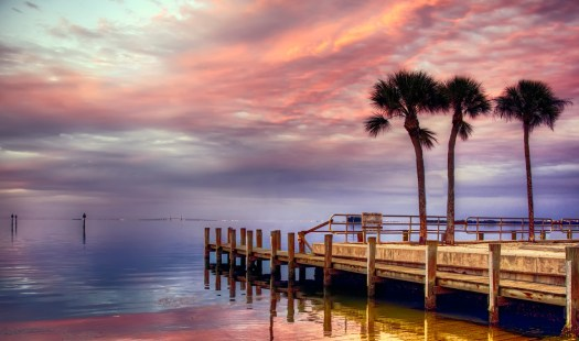 They call it the golden hour, but sometimes it's pink. A couple of weeks ago and looked over to see this scene right as the sun was setting. Not very golden is it. In fact it only looks like this once in a blue moon. Pink clouds, golden hour, blue moon; got all that? This is the public boat dock at Holmes Beach in Manatee County Florida.