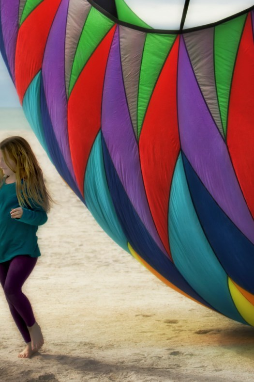 Another shot from the kite festival earlier this year at St Petes Beach Florida. In addition to standard kites, there were a few of these enormous balloon kites that bounced up and down in the breeze. And of course that's the perfect invitation to come play under the colorful billowy fabric. Of all the photos I took that day, the shots of the children playing around the kites were my favorite.
