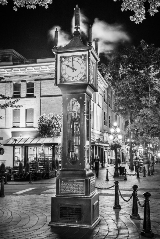 """This is a well-known steam clock in the Gastown section of Vancouver. I took this as I walked by on a warm summer evening last August.  Every ten or fifteen minutes the clock will begin blowing steam and the attached whistles will sound. As silly as that sounds it's really fun to wait it out, like waiting for a geyser. This is one of my favorite sections of town; with the old architecture it stands in contrast to the ultramodern architecture just two blocks away. It's said there used to be tunnels below the city that were used by the well heeled. Presumably they were used to convey """"businessmen"""" to the more seedy sections of town to satisfy out their whims and pleasures. Though with the way Vancouver has grown, what was once """"seedy"""" is now the pricier section of town. Perhaps if the tunnels still exist they are used in reverse?"""