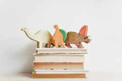 three dinosaurs on a stack of books