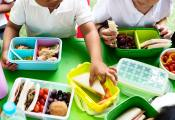 Children eating from their lunchboxes which have fruit and sandwiches