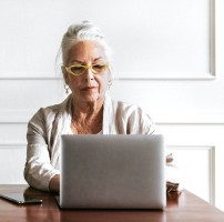 Old woman sat at a desk using a laptop