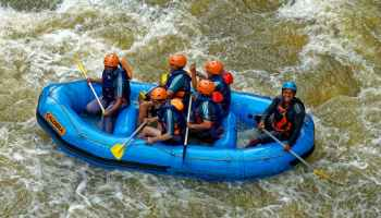 group of people riding blue raft on body of water