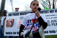 Kenny Jr. with the bullhorn in front of his father's banner, Annual Anti-Police Brutality March in Long Island, NY, Bay Shore, April 13th, 2013.