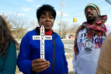 Danette holds a cross for victim, Jamal Blount. SpiritChild is to her right. Protesters march down 5th Avenue, demanding justice for police brutality victims. Annual Anti-Police Brutality March in Long Island, NY, Bay Shore, April 13th, 2013.