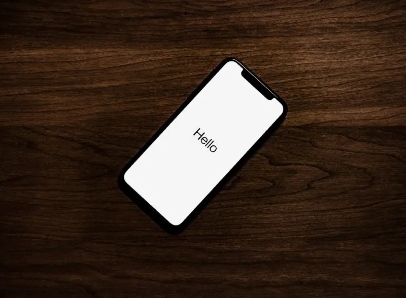 """""""turned on iPhone on top of brown wooden surface"""" by Tyler Lastovich on Unsplash"""