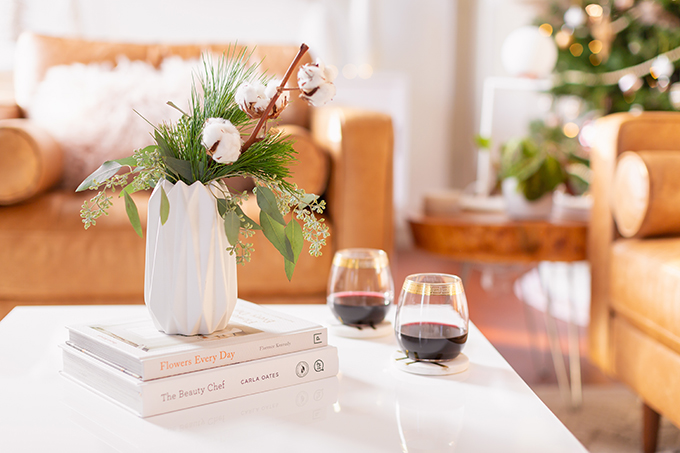 Apartment Friendly Modern Holiday Decor | Simple Holiday Arrangement on a Coffee Table with Greenery and Cotton Stems and 2 glasses of red wine with a Christmas Tree in the Background | Bohemian, Mid Century Modern Holiday Decor | Bohemian Holiday Home Tour 2018 | Canadian Tire CANVAS Ornaments // JustineCelina.com