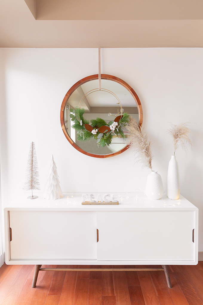 Apartment Friendly Modern Holiday Decor   DIY Modern Holiday Wreath with Magnolia Leaves, Cotton, Silver Dollar Eucalyptus, Seeded Eucalyptus, Cedar and Insense Cedar   Bohemian Holiday Home Tour 2018   Caramel Mid Century Modern Leather Couches   Canadian Tire CANVAS Ornaments // JustineCelina.com