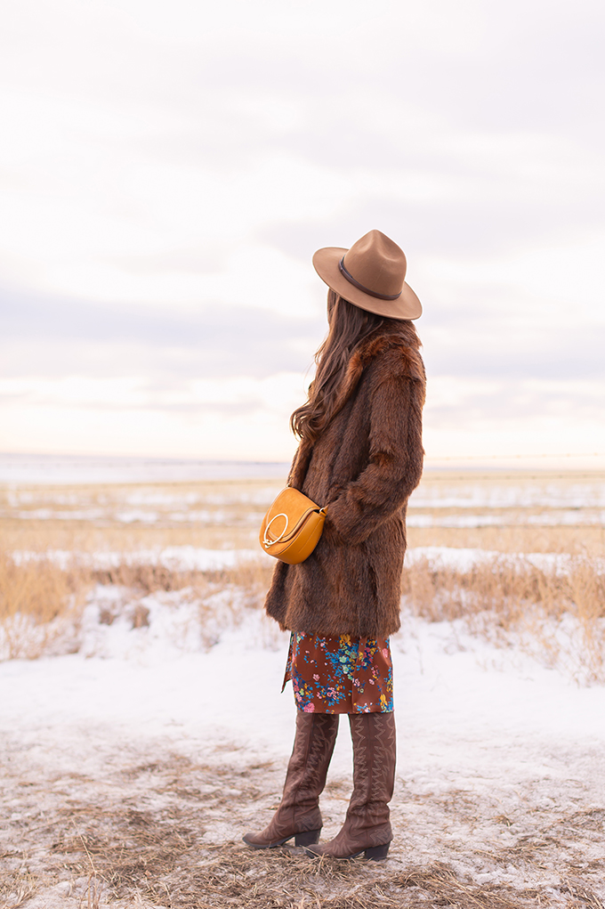 Pre Spring 2019 Trend Guide Bohemian Rhapsody: How to Style Midi Dresses for Transitional Spring Weather | Brunette Girl Standing in a Country Field at Sunrise Wearing a Brown Faux Fur Coat, Brown Floral Dress, Brown Wide Brim Hat and a Mustard Cross Body Bag | Bohemian Winter Style Ideas | Pantone Spring Summer 2019 Fashion Ideas | Calgary, Alberta, Canada Fashion & Lifestyle Blogger // JustineCelina.com
