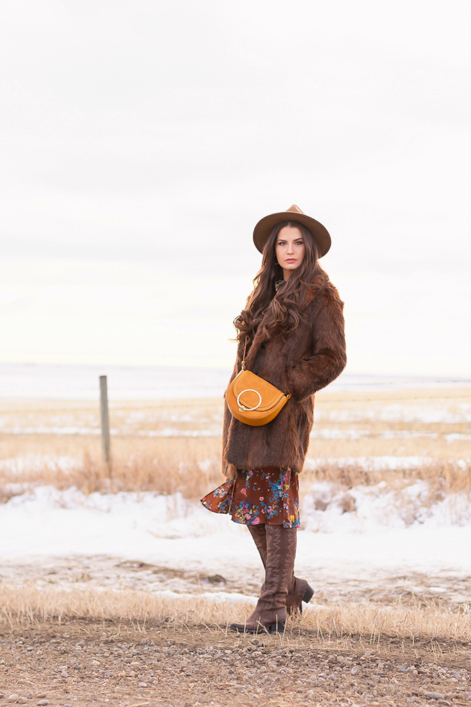 Pre Spring 2019 Trend Guide Bohemian Rhapsody: How to Style Midi Dresses for Transitional Spring Weather   Brunette Girl Standing in a Country Field at Sunrise Wearing a Brown Faux Fur Coat, Brown Floral Dress, Brown Wide Brim Hat and a Mustard Cross Body Bag   Bohemian Winter Style Ideas   Pantone Spring Summer 2019 Fashion Ideas   Calgary, Alberta, Canada Fashion & Lifestyle Blogger // JustineCelina.com