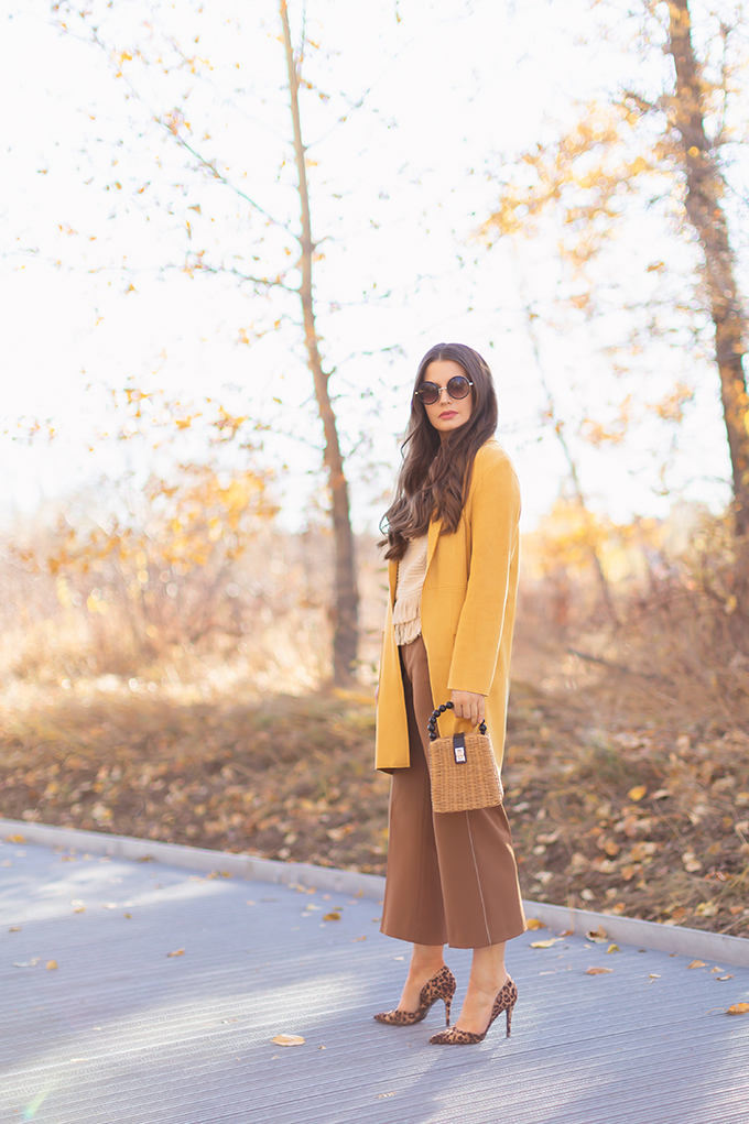 WORK WEAR   SPRING 2019 TRENDS AT THE OFFICE   How to Style Culottes for the Office   Brown 70's Style Culottes with a Mustard Faux Suede Jacket, Knit Fringe Hem Top, Natural Material Rattan Woven Box Bag and Leopard Print D'Orsay Heels   Spring 2019 Trends   Office Appropriate Spring Outfit Ideas // JustineCelina.com