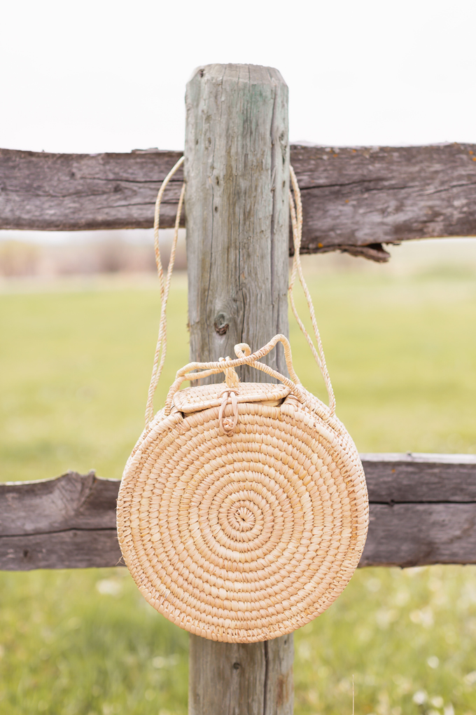 How to Style | Calgary's White Hat for The Stampede | A round rattan bag hanging on a western wooden fence in the country | Calgary Stampede Dress Code | Bohemian Western Inspired Outfit Summer 2019 | Boho Stampede Style | Justine Celina Maguire x Tourism Calgary // JustineCelina.com