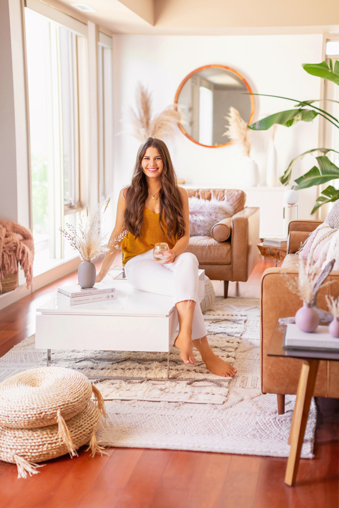 June 2019 Soundtrack | Smiling brunette woman enjoying a glass of white wine in her bright and airy mid century modern living room during the summer | The Best Summer 2019 Soundtracks | Summer 2019 Music | Brunette woman wearing a knit tank top and white cropped jeans sitting on her coffee table | JustineCelina's Inner City Calgary bohemian, mid-century modern apartment | Calgary Lifestyle + Interior Design Blogger // JustineCelina.com