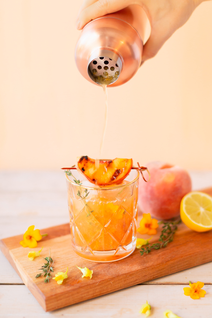 Smoked Peach Maple Bourbon Smash | A summer-meets-autumn sip juxtaposing juicy late summer fruit with a smoky grilled edge and spicy autumnal warmth | Dairy Free, Gluten Free and Refined Sugar Free -- and brimming with better-for-you ingredients! | The best fresh peach bourbon cocktail recipe | Grilled peach cocktail | Peach Bourbon Cocktail | Late summer bourbon cocktails | Southern Summer Peach Cocktail | Early Autumn Peach Cocktail | Autumn Equinox Cocktail Recipe // JustineCelina.com