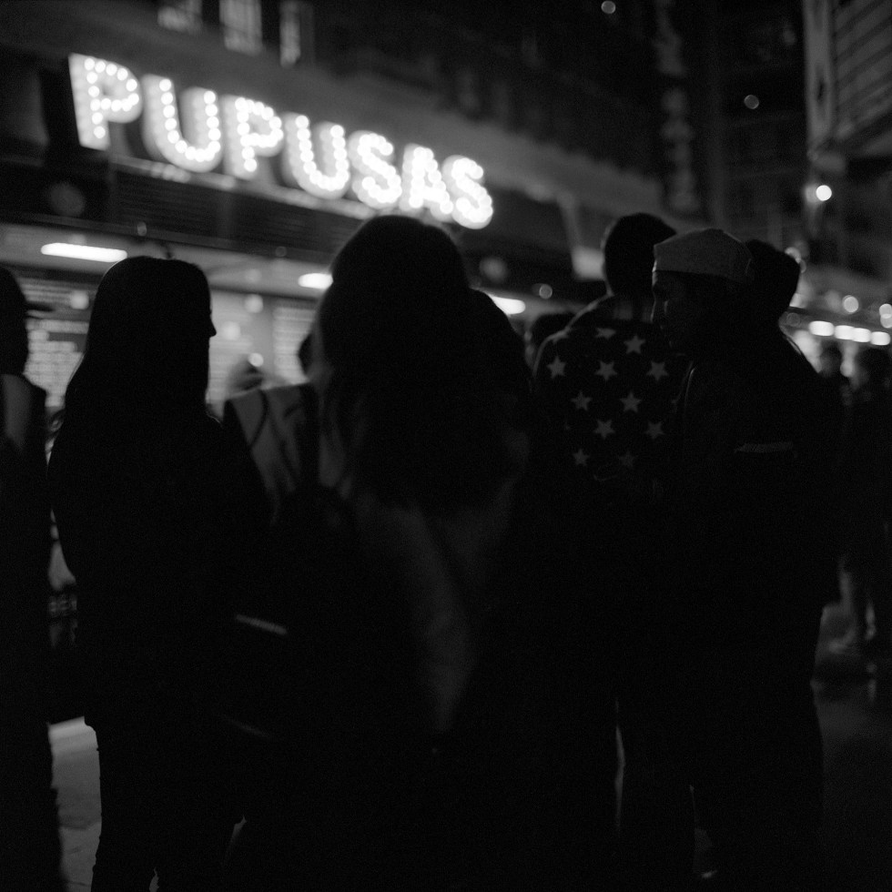 Silhouettes of people gathering to get pupusas from a food truck