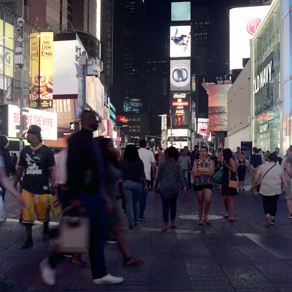 Crowds of people roam to and from places in Times Square at night