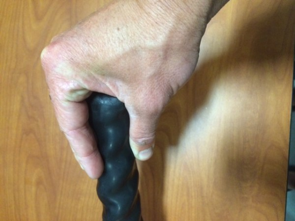 A mans hand pinching a battle rope with a black handle