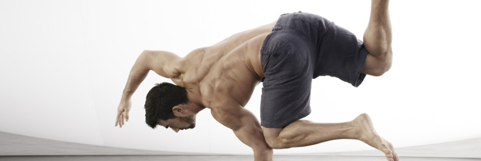 An very fit man balancing on his left arm