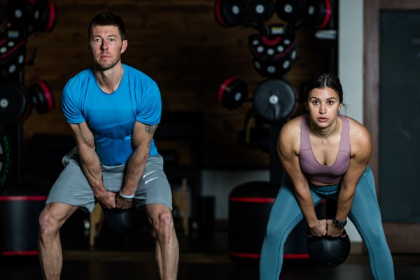 man and woman doing russian kettlebell swing