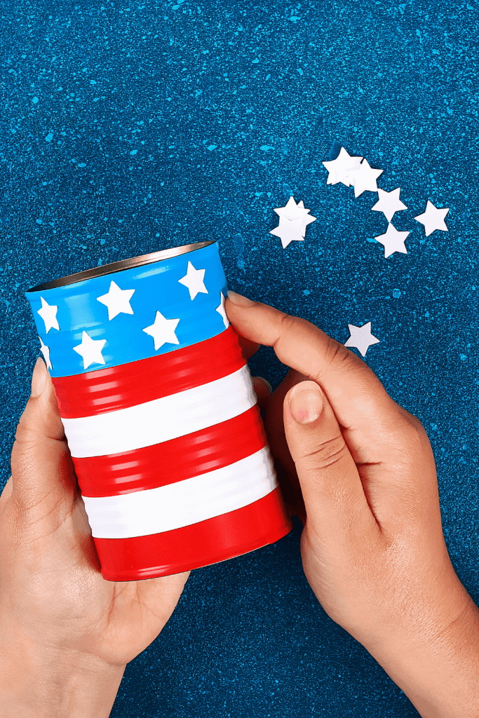 Make this DIY flag tin can to hold plastic forks and knives for your 4th of July party. Just take a clean old can and paint it or just tape for stripes. Then add patriotic star stickers! - Just Jes Lyn