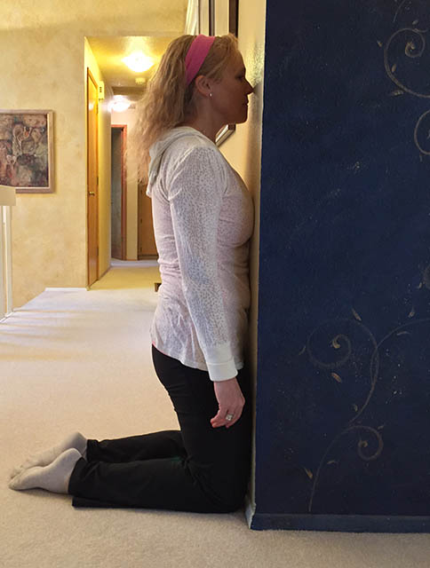 Image of Laura Coleman demonstration a kneeling wall excercise