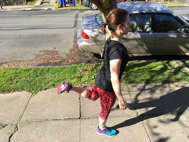 Image of woman-doing walking hamstring curls as part of pre exercise warmup routine