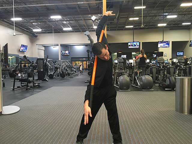 Image of man demonstrating shoulder and body twist exercise using a moving stick in a gym