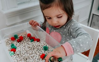 toddler using sensory bin