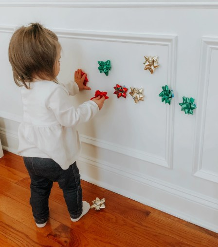 Easy Christmas activity using decorations in your home for your toddler. Use gift bows and stick to the wall to keep your toddler busy.